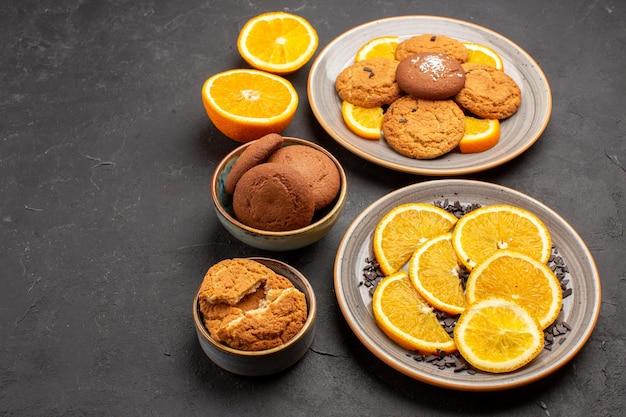 Vorderansicht köstliche sandkekse mit frisch geschnittenen orangen auf dunklem hintergrund zuckerkeks süßer keks-fruchtkuchen
