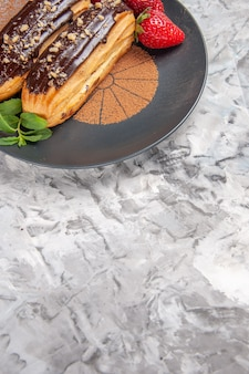 Vorderansicht köstliche schoko-eclairs mit erdbeeren auf leichten tischkuchen-dessert-keksen