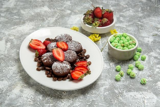 Vorderansicht köstliche schokoladenkuchen mit bonbons und erdbeeren auf weißer oberfläche kekszuckerkuchen süßer tee-keks