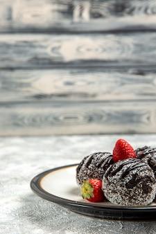 Vorderansicht köstliche schokoladenkuchen mit frischen roten erdbeeren auf der oberfläche schokoladenzuckerkeks süßer kuchen backen keks