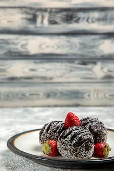 Vorderansicht köstliche schokoladenkuchen mit roten erdbeeren auf hellweißem wandschokoladenzuckerkeks süßer kuchen backen kekse