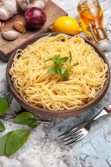 Vorderansicht köstliche spaghetti mit knoblauch auf einem weißen tisch nudelteig mahlzeit pfeffer