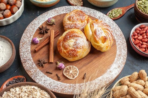 Vorderansicht köstliche süße brötchen mit nüssen auf grauer kuchenfarbe zuckerteigkuchen hotcake backtee