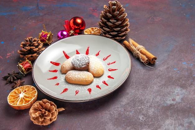 Vorderansicht köstliche süße kekse innerhalb des tellers auf dunklem raum