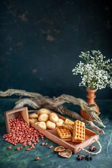 Vorderansicht köstliche süße kekse mit erdnüssen auf dunkler süßer kuchentorte zuckernuss