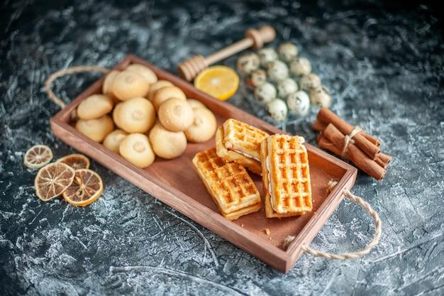 Vorderansicht köstliche süße kekse mit kleinen kuchen auf grauem süßem kuchenzuckerplätzchen-nusskuchen