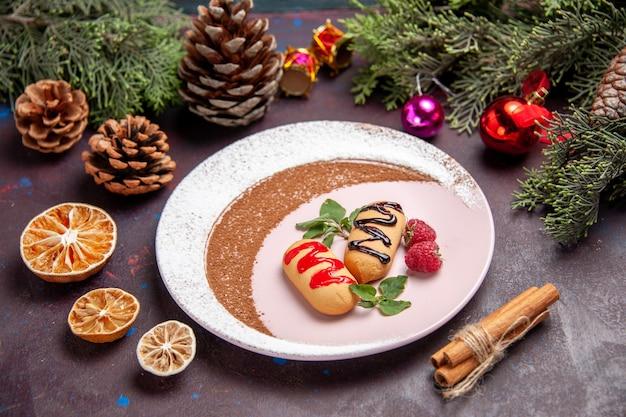 Vorderansicht köstliche süße kekse mit weihnachtsspielzeug auf dunklem raum