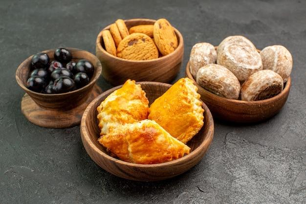 Vorderansicht köstliche süße kuchen mit keksen und oliven auf dunkler oberfläche süße kuchen torte