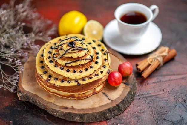 Vorderansicht köstliche süße pfannkuchen mit tasse tee auf dem dunklen hintergrund