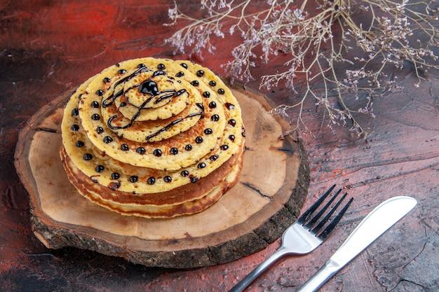 Vorderansicht köstliche süße pfannkuchen mit zuckerguss auf dunklem hintergrund