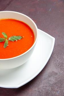 Vorderansicht köstliche tomatensuppe leckeres gericht mit einzelnem blatt im teller auf dunklem schreibtischgericht soße tomatenfarbensuppe
