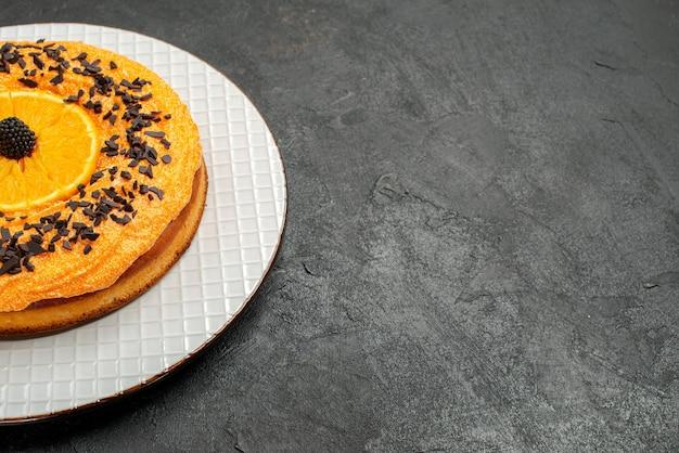 Vorderansicht köstliche torte mit schokoladenstückchen und orangenscheiben auf dunklem hintergrund teetorte dessertkuchen obstkeks