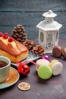 Vorderansicht köstliche torte mit tasse tee auf dunklem hintergrund kuchen zuckerkekse torte süßer keks tee