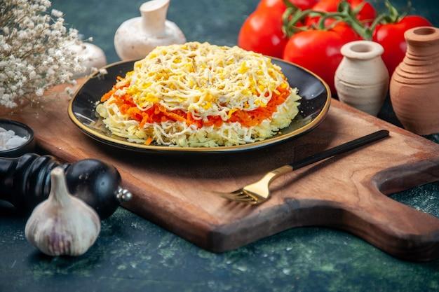 Vorderansicht köstlichen mimosensalat innerhalb platte mit tomaten auf dunkelblauer oberfläche feiertagsmahlzeit farbe küche essen geburtstag fleisch küche foto