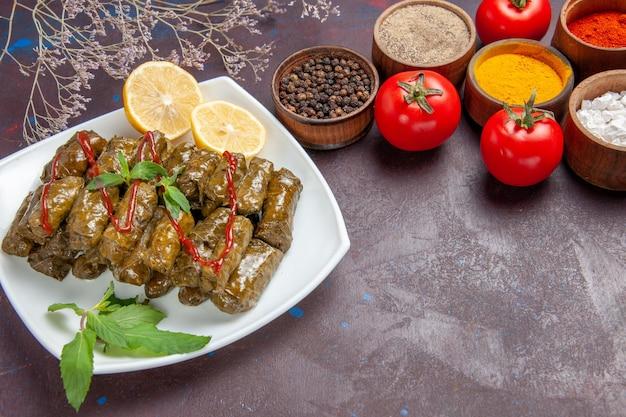 Vorderansicht köstlicher blattdolma mit gewürzen und tomaten auf dunklem raum