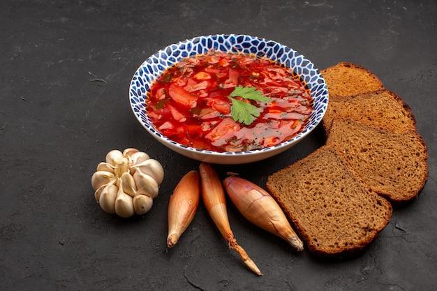 Vorderansicht köstlicher borschtsch mit dunklen brotlaiben auf dunklem raum