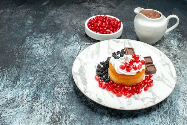 Vorderansicht köstlicher cremiger kuchen mit schokolade und rosinen auf hell-dunklem hintergrund zuckerplätzchen kekse dessert süß