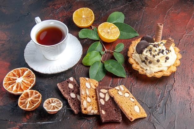 Vorderansicht köstlicher cremiger kuchen mit tasse tee auf dunklem hintergrund