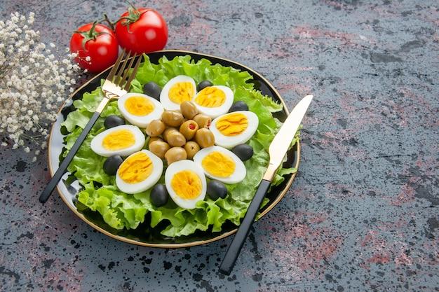 Vorderansicht köstlicher eiersalat mit tomaten und oliven auf hellem hintergrund