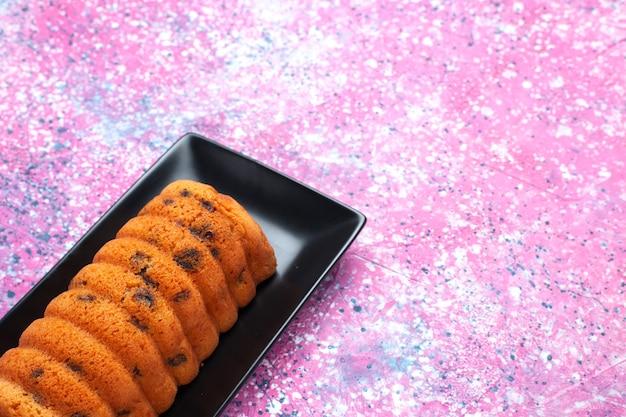 Vorderansicht köstlicher gebackener kuchen innerhalb der schwarzen kuchenform auf rosa hintergrund.