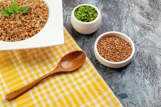 Vorderansicht köstlicher gekochter buchweizen innerhalb einer weißen platte mit grüns auf einer hellgrauen lebensmittelkalorienmahlzeit fotoschale bohnenfarbe