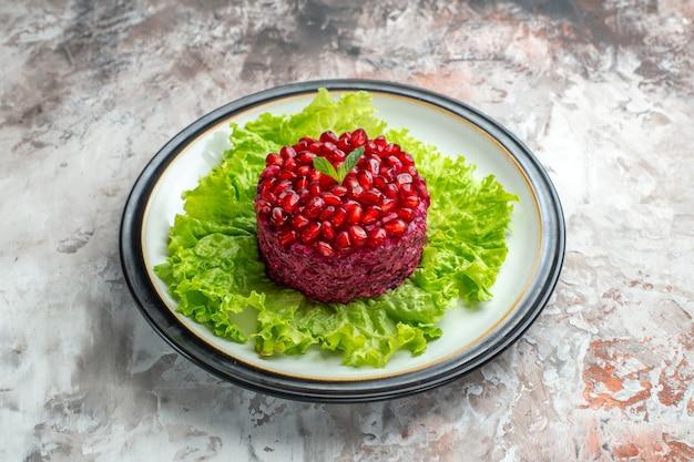 Vorderansicht köstlicher granatapfelsalat rund geformt auf grünem salat auf hellem hintergrund