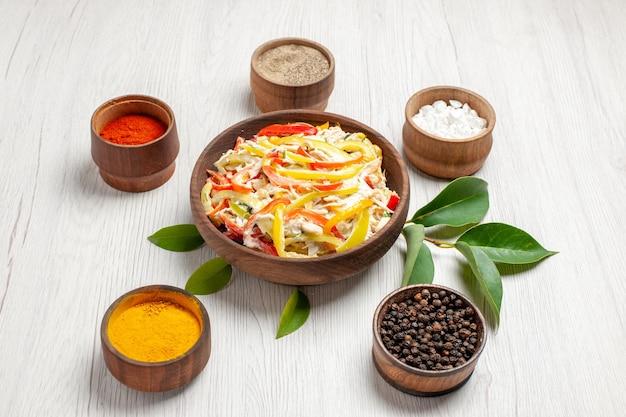 Vorderansicht köstlicher hühnersalat mit verschiedenen gewürzen auf weißem schreibtischsnack reife mahlzeit fleisch frischer salat