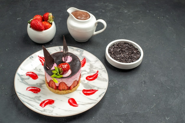 Vorderansicht köstlicher käsekuchen mit erdbeere und schokolade auf ovaler tellerschüssel mit erdbeeren und schokolade auf dunklem