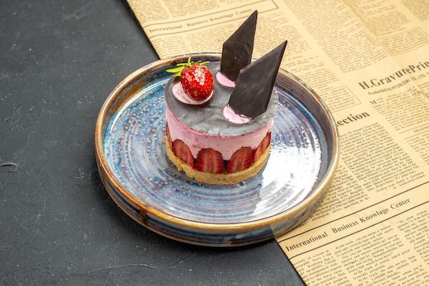 Vorderansicht köstlicher käsekuchen mit erdbeere und schokolade auf teller eine zeitung auf dunklem freien platz