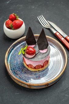 Vorderansicht köstlicher käsekuchen mit erdbeere und schokolade auf tellerschüssel mit erdbeergabelmesser auf dunkel