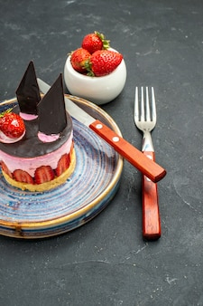 Vorderansicht köstlicher käsekuchen mit erdbeere und schokolade ein messer auf einer tellerschüssel mit erdbeeren eine gabel auf dunkel