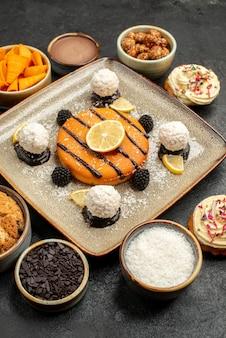 Vorderansicht köstlicher kleiner kuchen mit kokosbonbons auf dunklem hintergrund teekuchen keks keks kuchen dessert