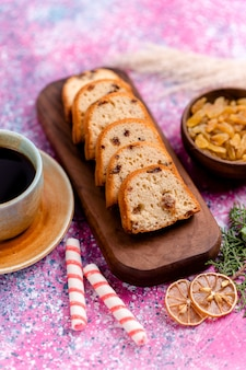 Vorderansicht köstlicher kuchen geschnittener kuchen mit rosinen und mit tasse kaffee auf rosa schreibtisch backen kuchen zucker süßer keks-keks