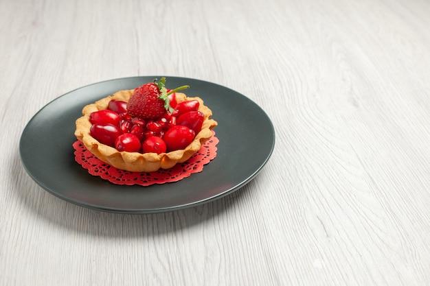 Vorderansicht köstlicher kuchen mit frischen früchten auf weißem schreibtischkuchen-dessertfruchtrot