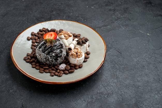 Vorderansicht köstlicher kuchen mit keksen und schokoladenstückchen auf dunkelgrauem oberflächenkuchenzuckerbackkeks-süßem keks