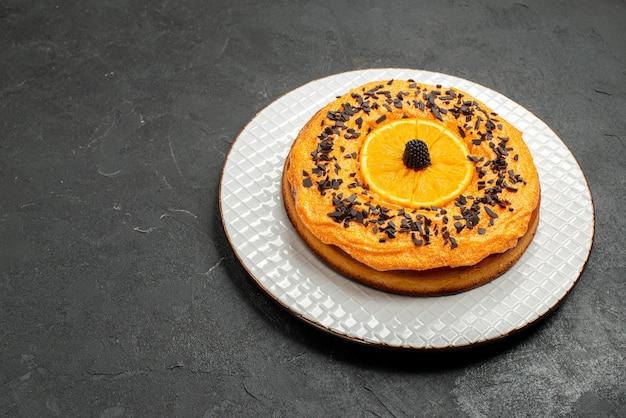Vorderansicht köstlicher kuchen mit schokoladenstückchen und orangenscheiben auf dunklem hintergrund dessertkuchen kuchen obstkeks