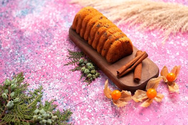 Vorderansicht köstlicher kuchen süß und lecker mit zimt auf dem rosa schreibtisch.