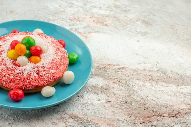 Vorderansicht köstlicher rosa kuchen mit bunten bonbons im teller auf weißem hintergrund kuchen regenbogenfarben kuchen dessert süßigkeiten rainbow