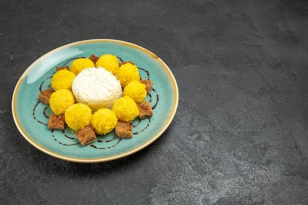 Vorderansicht köstliches dessert kleine gelbe bonbons mit kuchen in der platte auf dem grauen hintergrund süßigkeiten tee zuckerkuchen süß