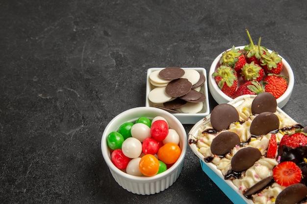 Vorderansicht köstliches dessert mit süßigkeiten kekse und erdbeeren auf dunklem hintergrund nusskeks süße fruchtplätzchen zucker