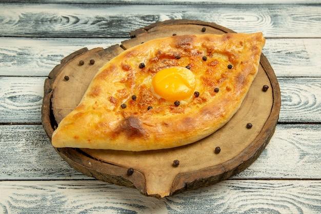 Vorderansicht köstliches eierbrot, das auf einem rustikalen grauen raum gebacken wird