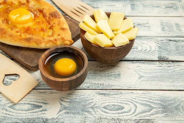 Vorderansicht köstliches eierbrot, das auf einem rustikalen schreibtisch gebacken wird