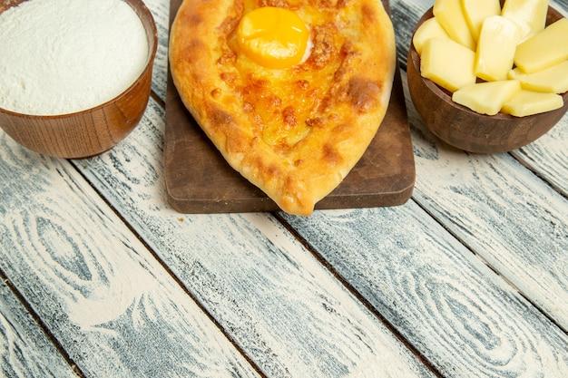 Vorderansicht köstliches eierbrot mit mehl und käse auf einem rustikalen schreibtisch gebacken