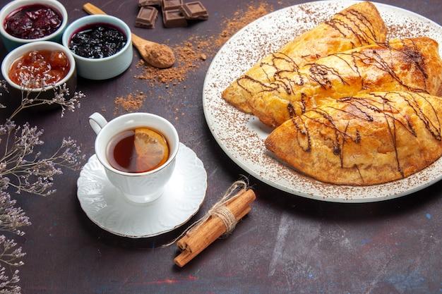 Vorderansicht köstliches gebackenes gebäck mit tasse tee und marmelade auf dunklem raum