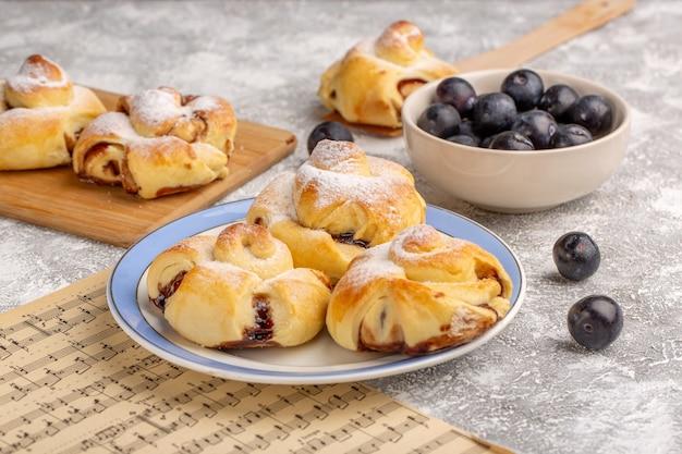 Vorderansicht köstliches gebäck mit füllung innenplatte zusammen mit frischen schwarzdorn auf weißem tisch, süßer kuchen backen gebäck