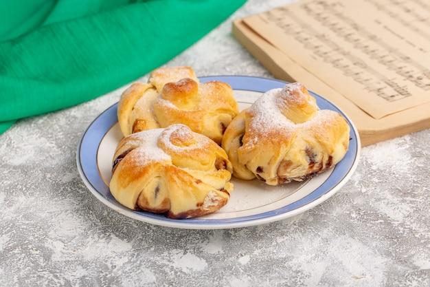 Vorderansicht köstliches gebäck mit füllung innerhalb platte auf dem weißen tisch, süßer kuchen backen gebäckfrucht