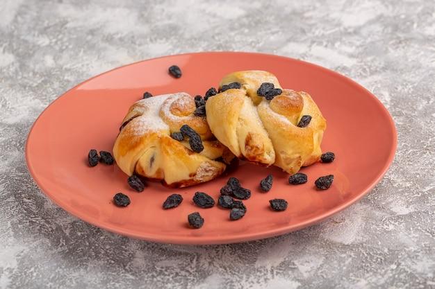 Vorderansicht köstliches gebäck mit füllung innerhalb platte zusammen mit getrockneten früchten auf weißem tisch, süßer zuckerkuchen backen gebäck