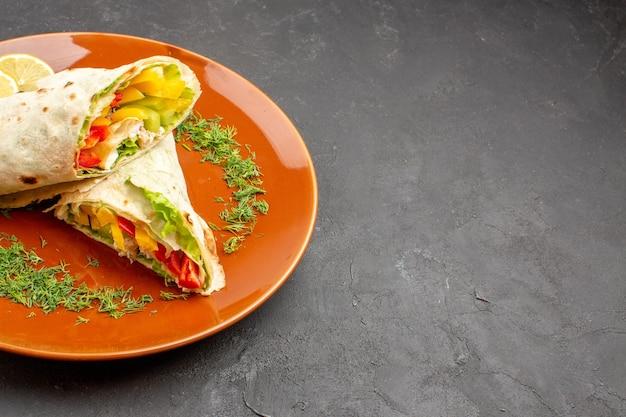 Vorderansicht köstliches geschnittenes shaurma-salat-sandwich innerhalb des tellers auf dem dunklen raum