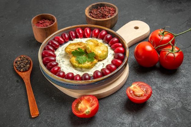 Vorderansicht köstliches kürbismehl mit frischen roten hartriegel-tomaten und gewürzen auf grauzone