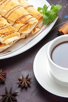 Vorderansicht köstliches süßes gebäck mit tasse tee auf dunklem raum